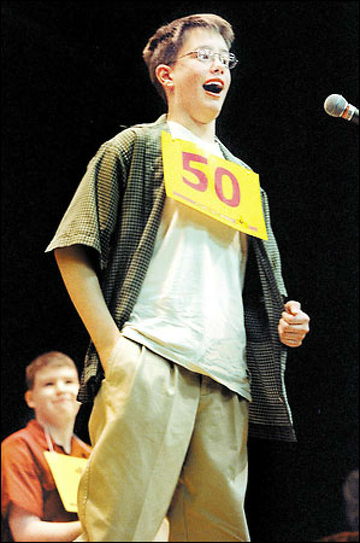 Washington Middle School eighth-grader Patrick Daughters wins the regional spelling bee championship for King and Snohomish counties at Seattle University yesterday over second-place Christopher Richards, in background.