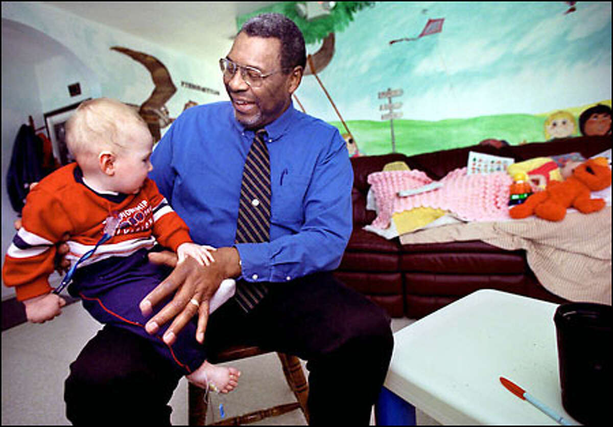 Dr. Isaac Pope plays with 7-month-old Nate Wood at Pope's Kids Place, a children's center he created in Centralia.