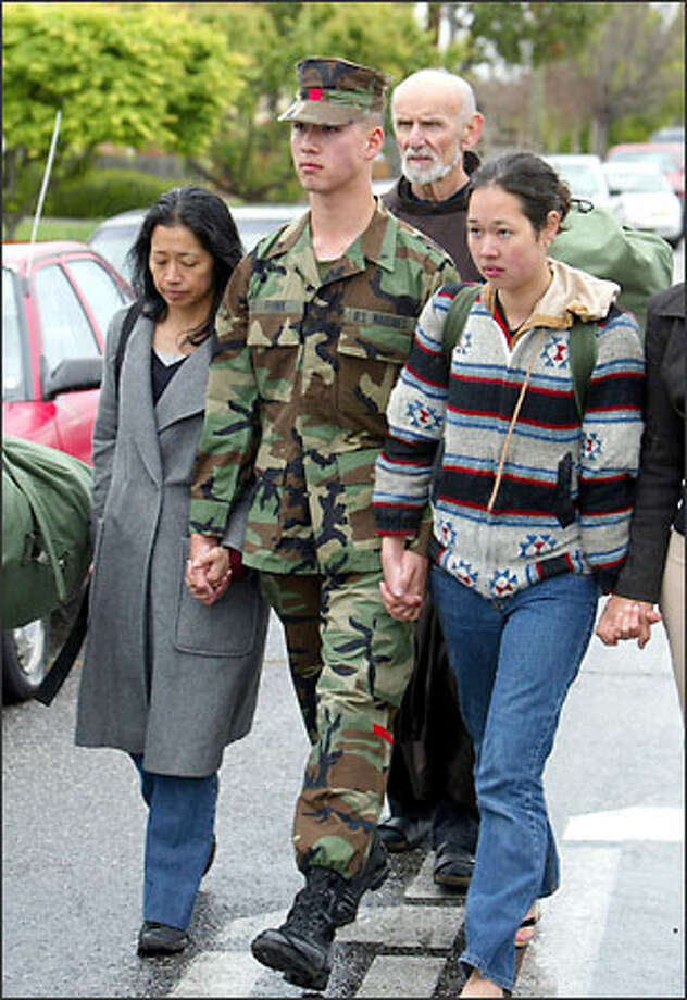 Marine Corps reservist Stephen Funk, center, walks with his mother, Gloria Pacis, left, and sister Caitlin Funk to turn himself in at his reserve unit in San Jose, Calif. Photo: Associated Press / Associated Press