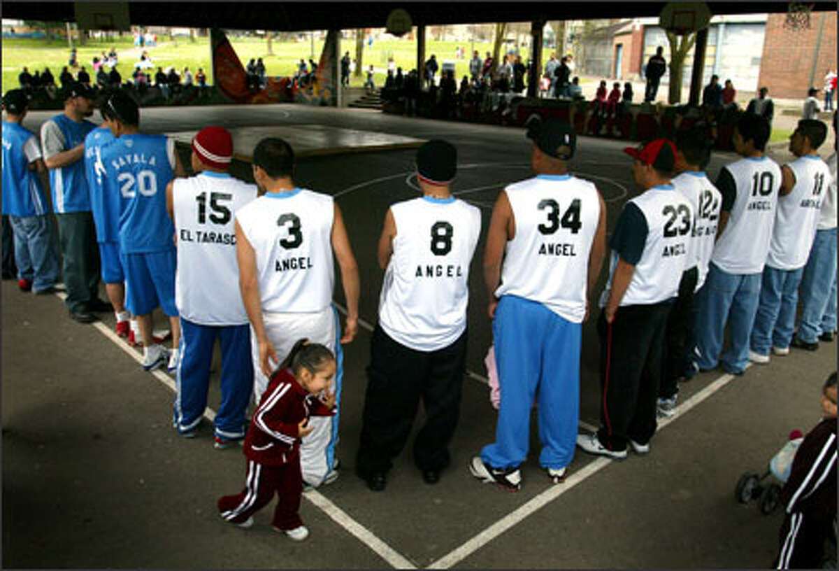 Players from Michoacan are introduced to the crowd of about 200 during opening ceremonies Sunday at a park in the Central District. The social-service agency El Centro de la Raza helped Liga Latina de Basketball find an indoor court for its fall tournament.