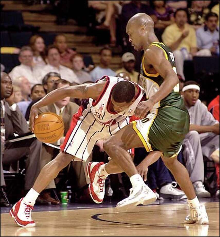 Houston's Steve Francis, left, tries to drive past Gary Payton in the first half. Photo: Associated Press / Associated Press