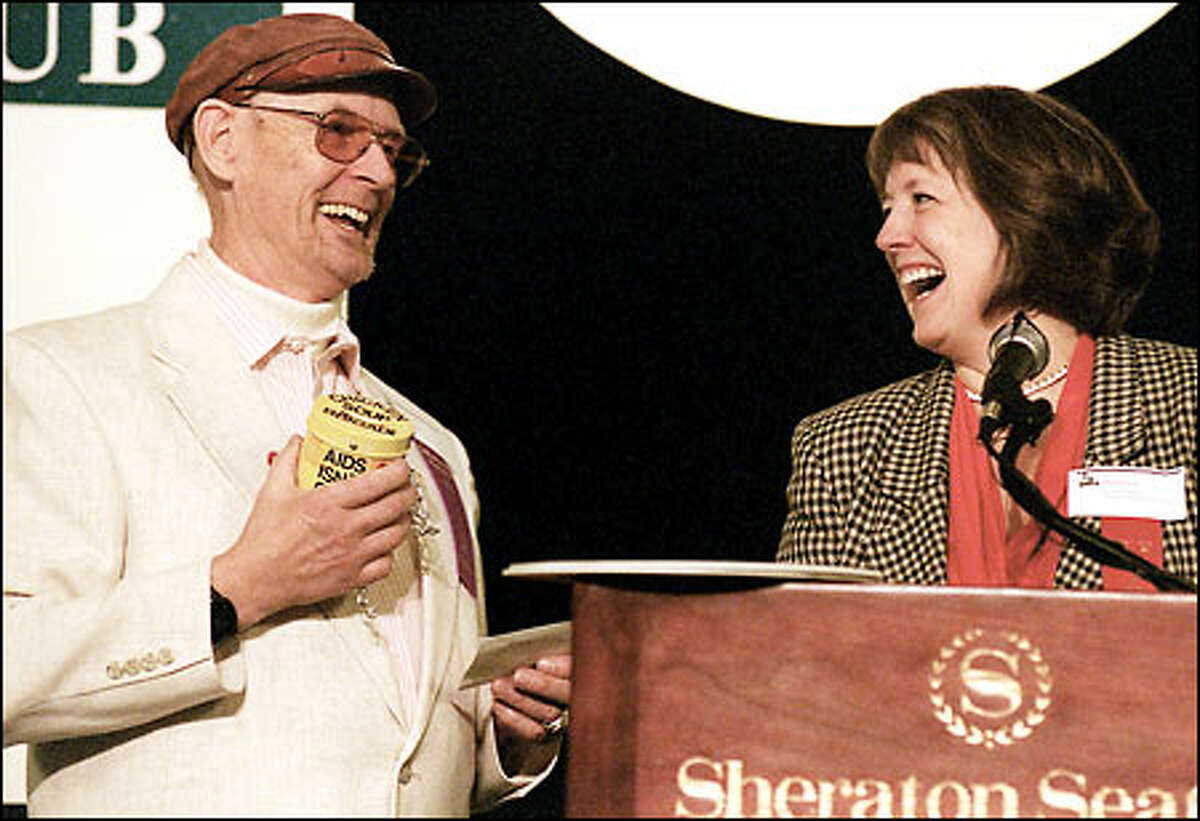 Lenny Larson holds a Chicken Soup Brigade coin jar as he accepts a Jefferson Award from state Supreme Court Justice Barbara Madsen. Larson, who has worked to provide support to people with AIDS, was one of six people honored in the ceremony at the Sheraton Seattle Hotel & Towers.