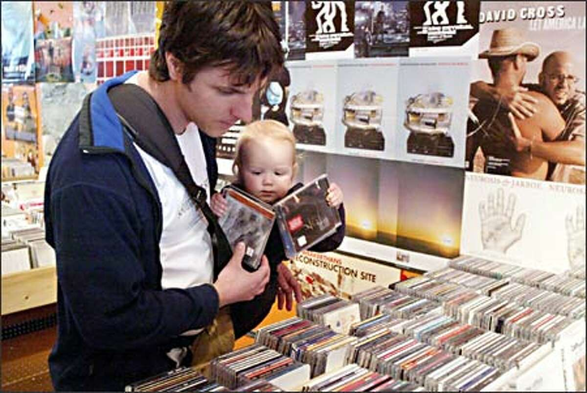 Andy Bauck, with 14-month-old son Levi, scours CDs at Sonic Boom Records' Capitol Hill store, one of three locations the local company operates.