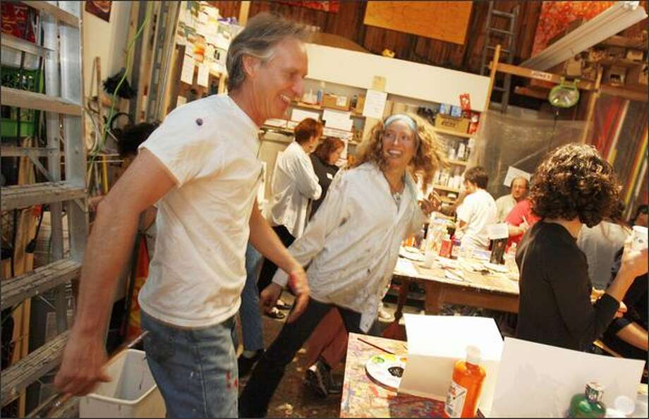 Local artist Matt Jones dances with Karen Fletcher at his studio at the Gasworks Gallery during the monthly paint-dancing event. Jones, an abstract painter, doles out acrylic paint and paper, cranks up the music and gets people to boogie while they get artistic. Photo: Gilbert W. Arias, Seattle Post-Intelligencer / Seattle Post-Intelligencer
