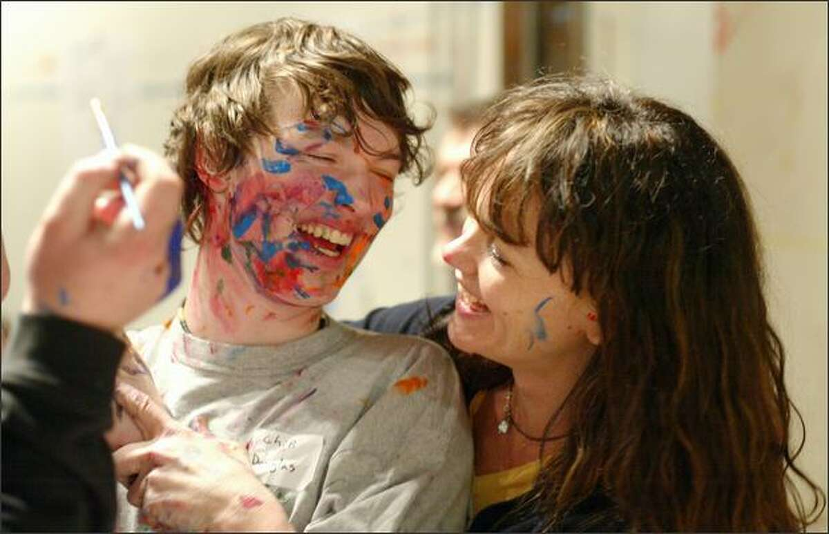 Zach Andrich, center, laughs with his mother, Shamay Andrich, during an impromptu face-painting session during the monthly paint-dancing event at the Gasworks Gallery on Friday March 14, 2008.