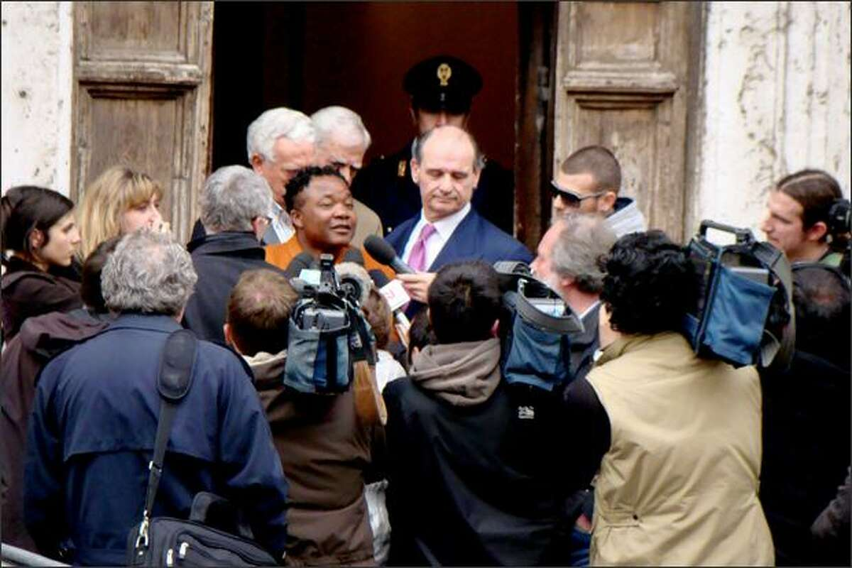 """Diya """"Patrick"""" Lumumba takes press questions outside the courthouse in Perugia after giving testimony before the jury."""