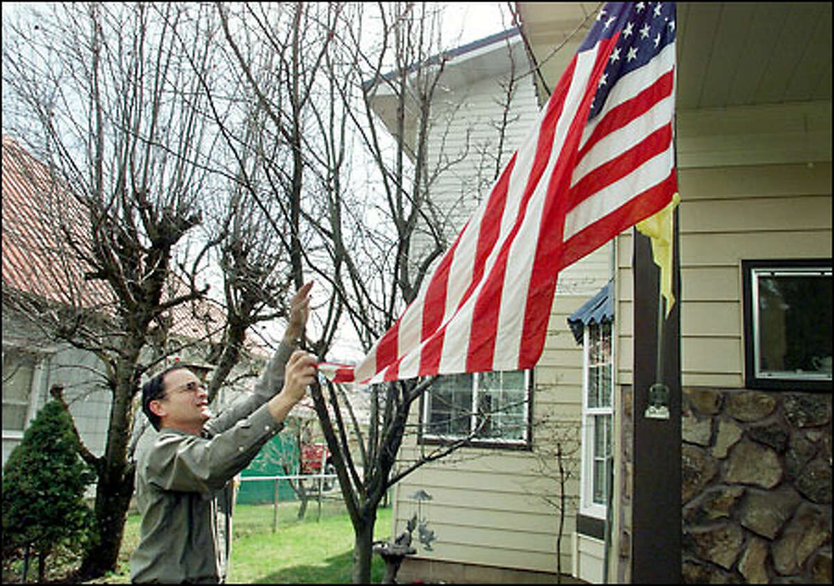 """Mike Cecka, father of Aviation Electronics Technician David Cecka, who is being detained in China, untangles the flag outside his Cle Elum home. David Cecka, 28, who grew up in Leavenworth, recently re-enlisted in the Navy. Mike Cecka says his son has not said much about his job aboard the """"spy plane."""""""