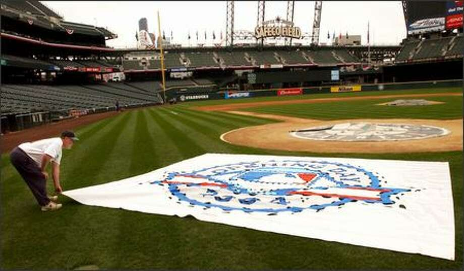 Mariners groundskeeper Bob Christofferson adjusts the template used to paint the Opening Day logo behind home plate. Photo: Jeff Larsen, Seattle Post-Intelligencer / Seattle Post-Intelligencer