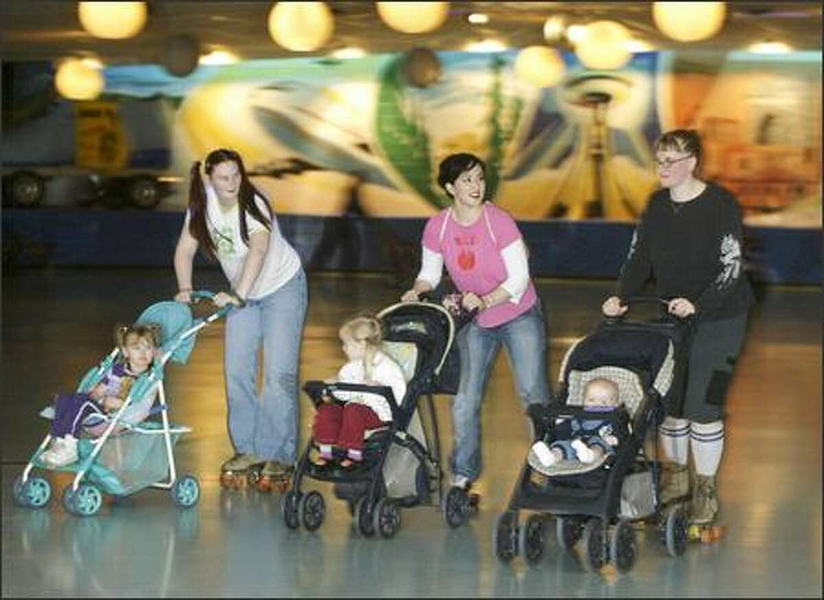 Seattle Punkymoms meet for a stroller skate in Bellevue: from left, Heather Bissonnette and daughter Jessica Henderson, 3; Thea Starr and daughter Nievis, 3; and Jessi Bloom-Kenney with 6-month-old Micah.