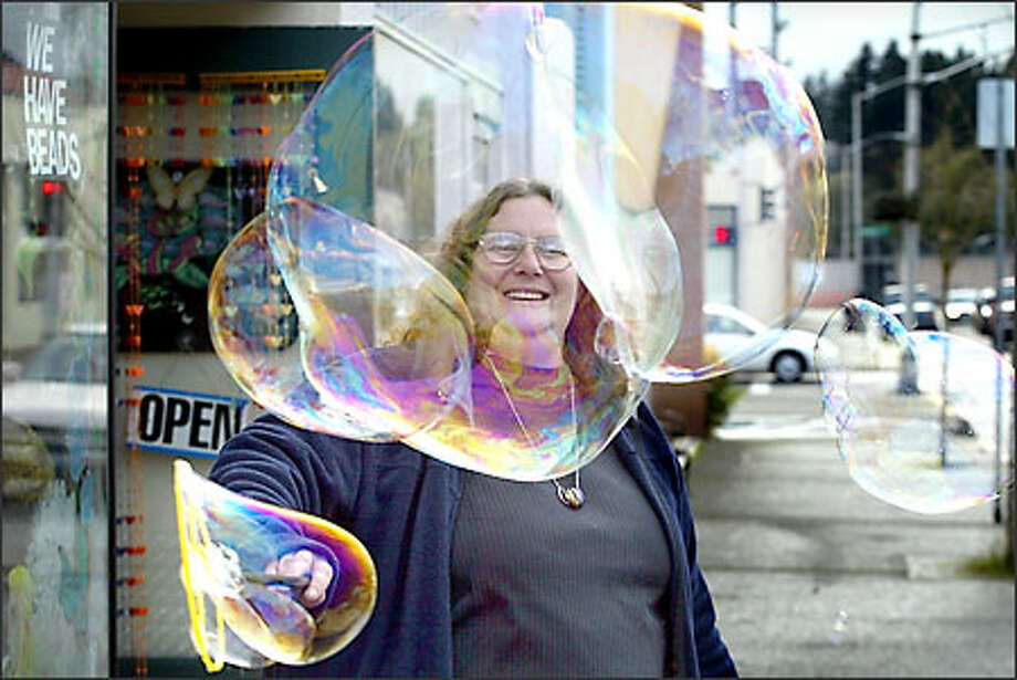 Jane Heath, manager of the gift shop Chrysalis, creates some bubble magic in front of her store on Legion Way Southwest in Olympia. The shop caters to college students living in the area and sells beads, incense, candles, crafts and other novelties. Chrysalis is one of several businesses participating in the Olympia Arts Walk, a free event at more than 100 downtown venues the third Friday and Saturday in April. Arts Walk highlights the work of over 500 visual, performing and literary artists. Photo: Gilbert W. Arias, Seattle Post-Intelligencer / Seattle Post-Intelligencer