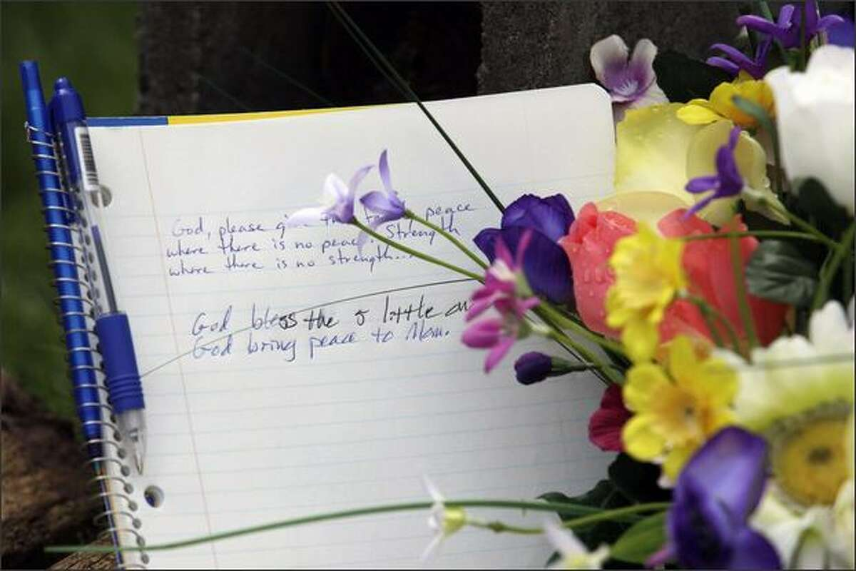 A message is shown in a notebook at a memorial in front of the home were five children were discovered killed on Saturday at a trailer park near near Graham, Wash. Pierce County Sheriff's officials said they believe the children's father killed the children before committing suicide. (AP Photo/Ted S. Warren)