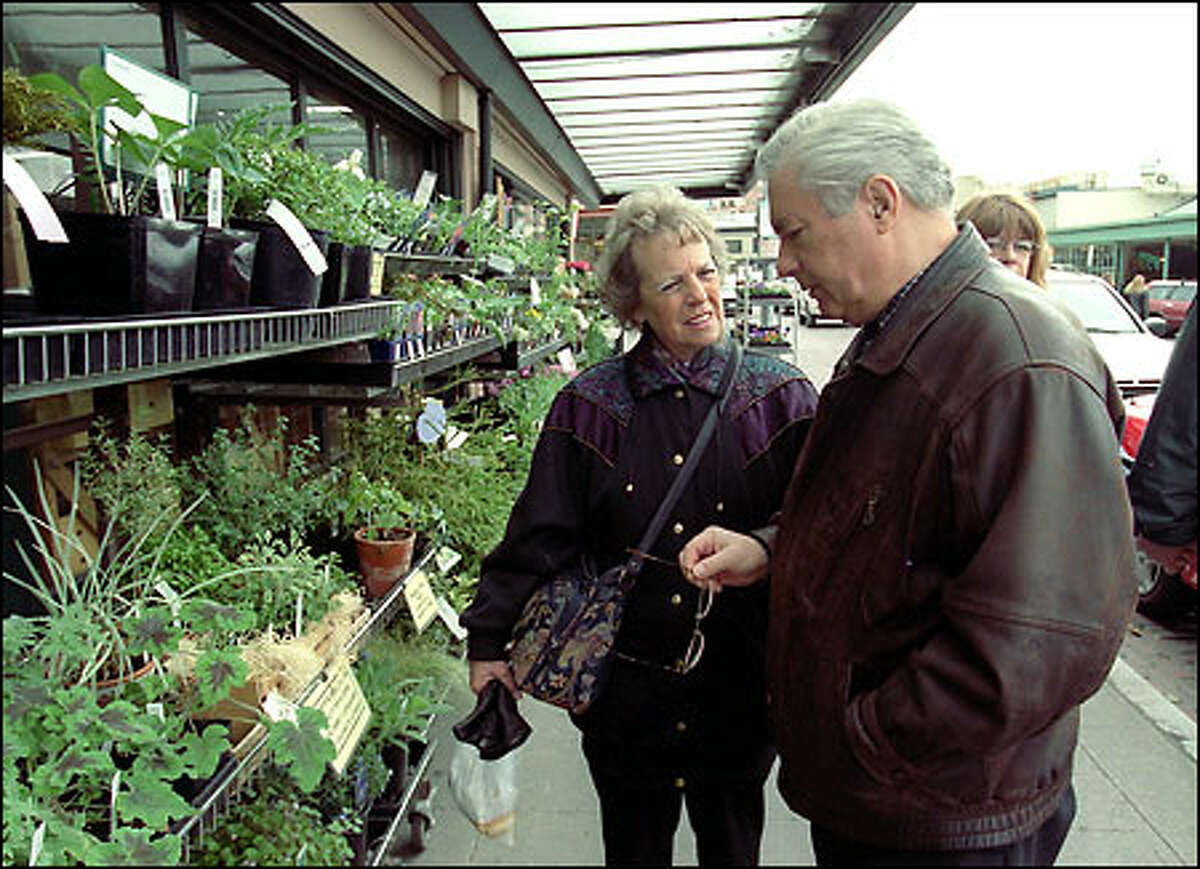 Hazel and Roger Kingston of England shop at the Seattle Garden Center store at the Pike Place Market. The new owner will have to adhere to rules governing the historic area.