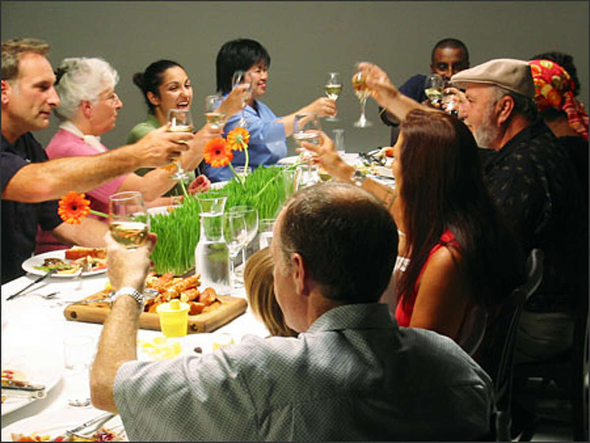 """Participants in the three-part PBS series """"The Meaning of Food"""" toast as they share a meal. The documentary has several Washington state segments, one of which features P-I food editor Hsiao-Ching Chou, in the blue blouse, center. (PIE IN THE SKY PRODUCTIONS)"""