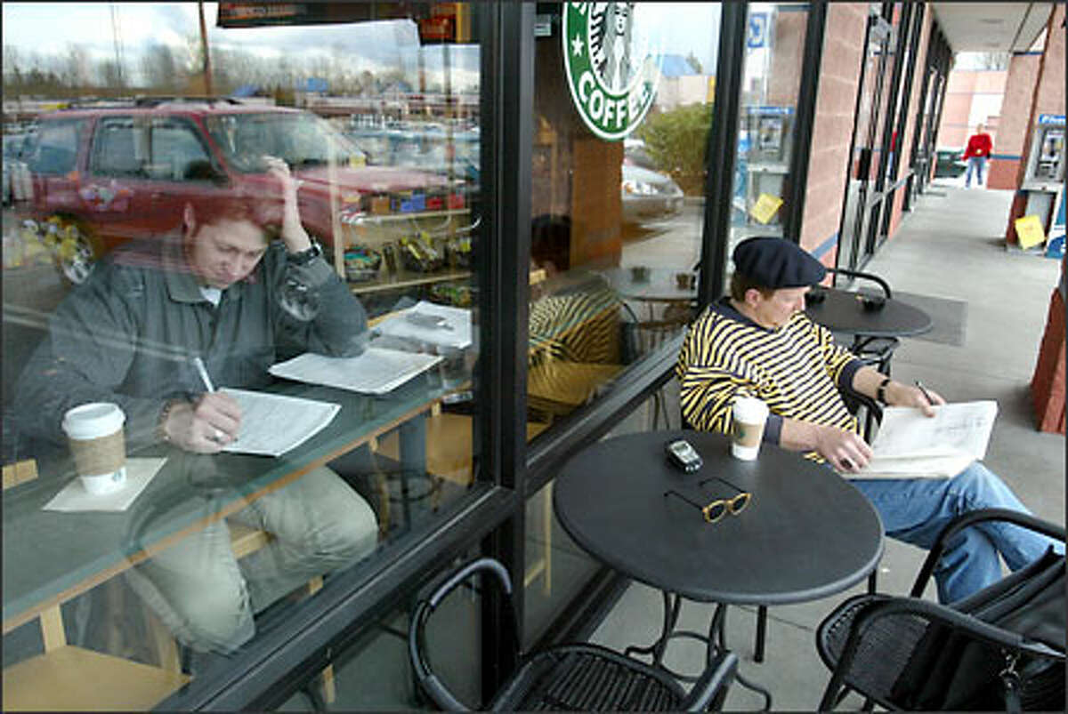 James Sundin, right, and Mark Ford, both of Seattle, could be sipping their lattes in different cities while sitting at the same Starbucks on Pacific Highway South.