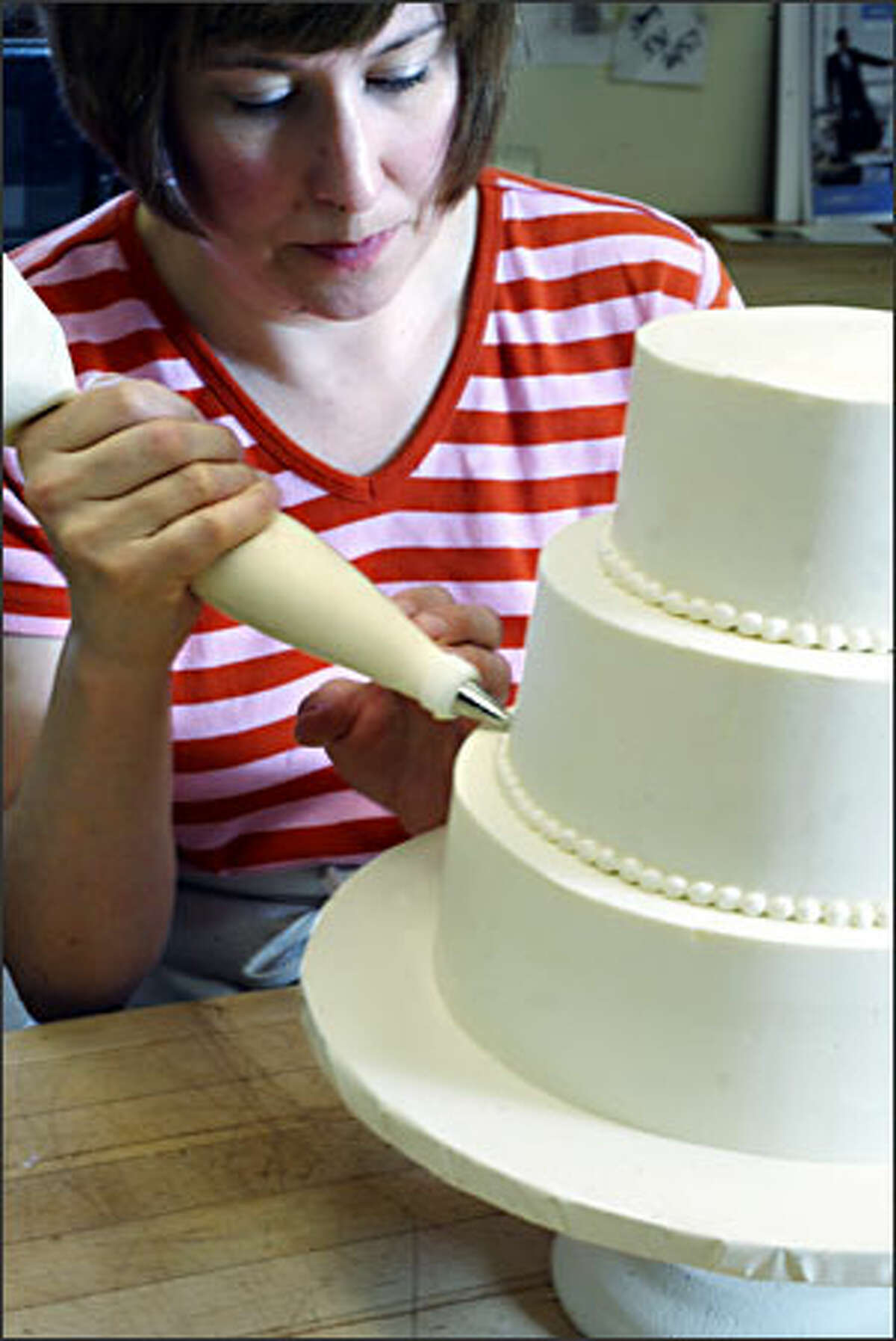 Bonnie Lyons, pastry chef and owner of New Renaissance Cakes, works piping beads around one of her cakes. This style is an example of the starting-price cake. It costs $272, with delivery included, and serves 64.
