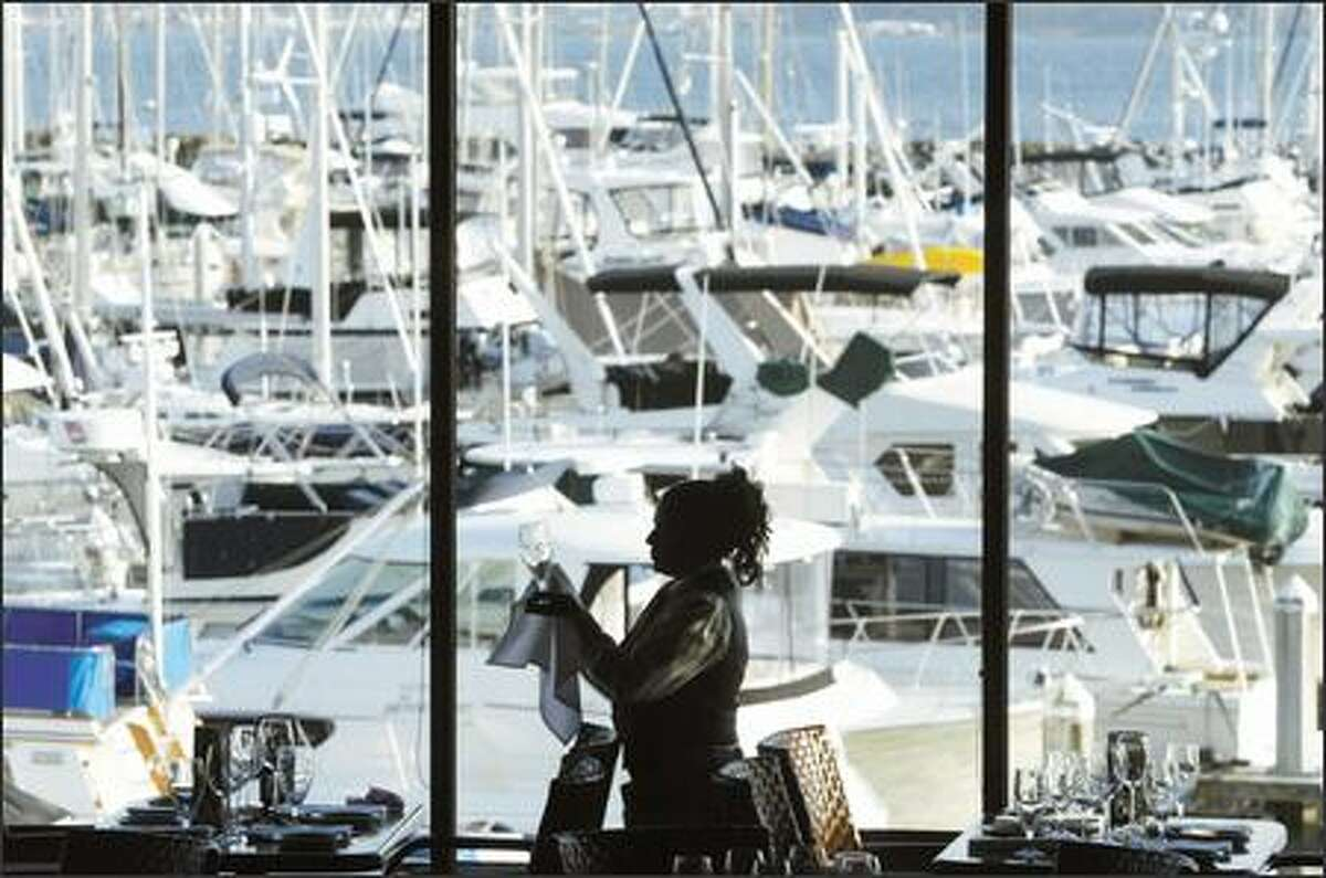 The pleasure boats berthed at Elliott Bay Marina serve as a backdrop as Palisade server Cynthia Andersen polishes a wine glass before dinner.
