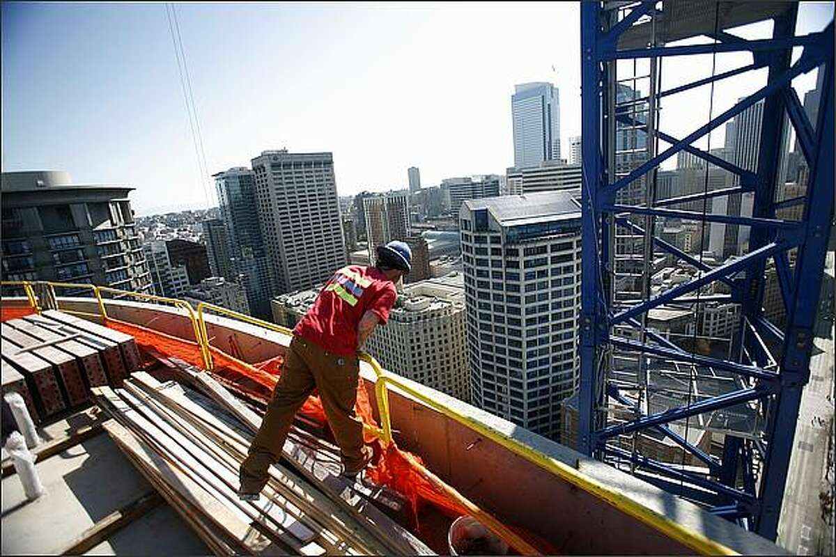 A construction worker looks over the edge of Escala, a new 31-story condo tower at 4th Avenue and Virginia Street in downtown Seattle. When completed the building will be downtown Seattle's largest housing structure.