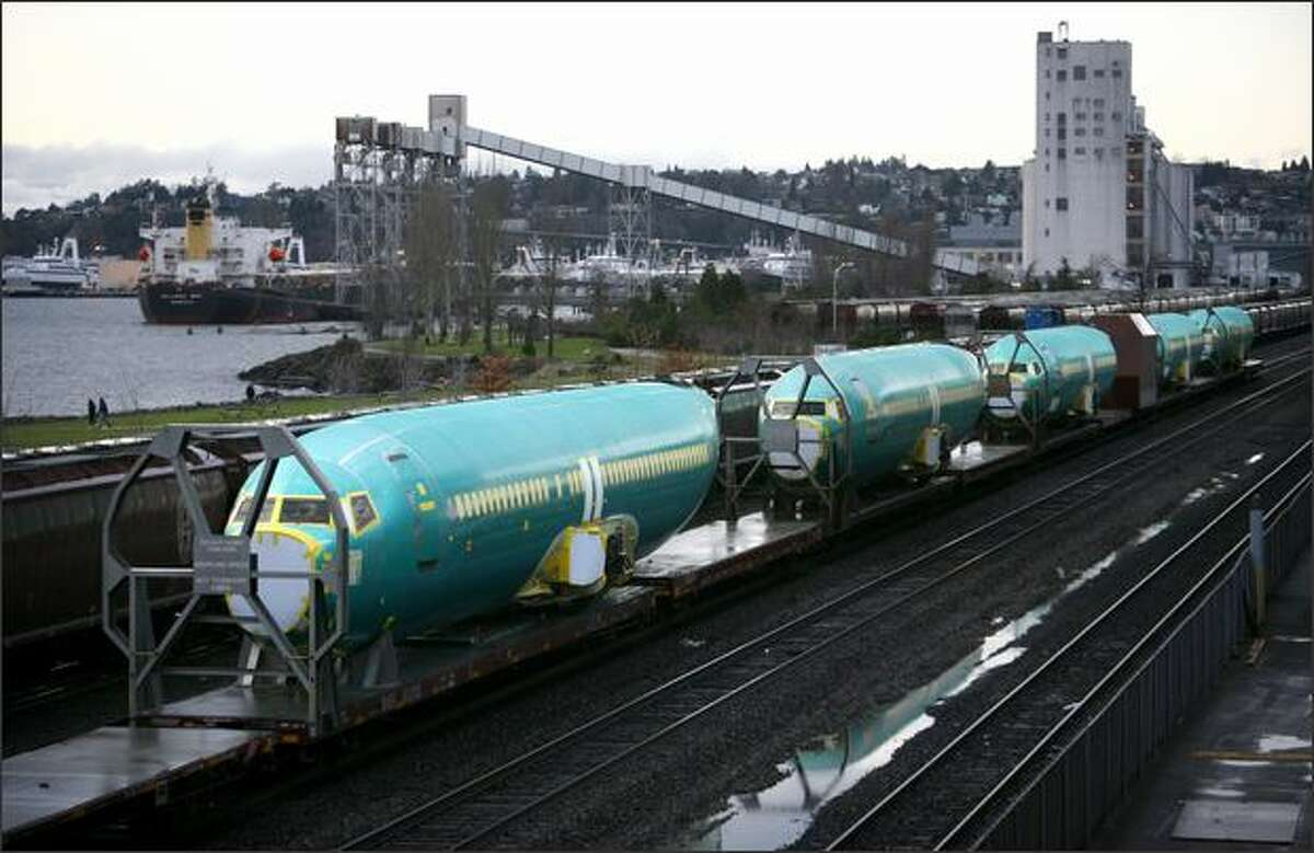 A train loaded with Boeing airplanes travels along the waterfront in Seattle.