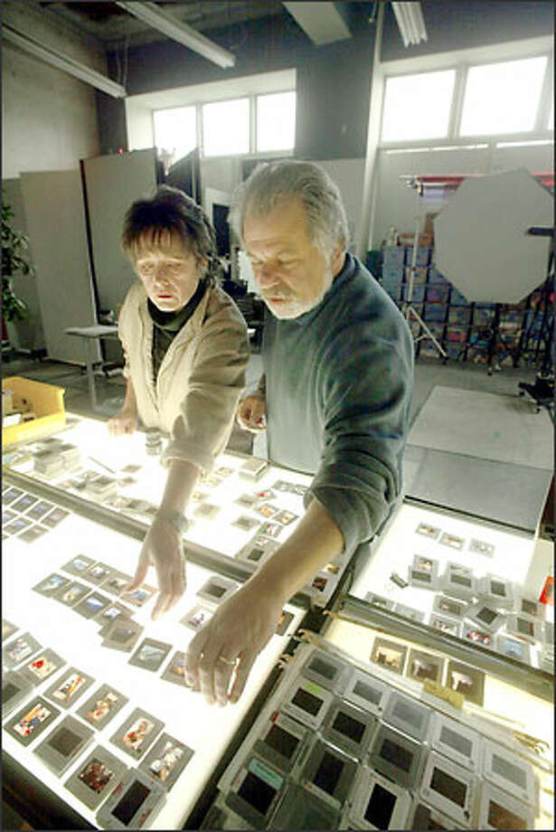"Pat Kane and Gabe Palmer, owners of Postcards from the Moon, look over slides for their next line of cards. The couple started the company in 2000 after a cross-country trip with their son. During that trip, Palmer created prints that became the company's first card collection. They recently opened a Capitol Hill store and studio at 1525 Summit Ave. Postcards from the Moon, which won a ""card of the year"" award last year, is a finalist for the same honor again this year. Photo: Phil H. Webber, Seattle Post-Intelligencer / Seattle Post-Intelligencer"