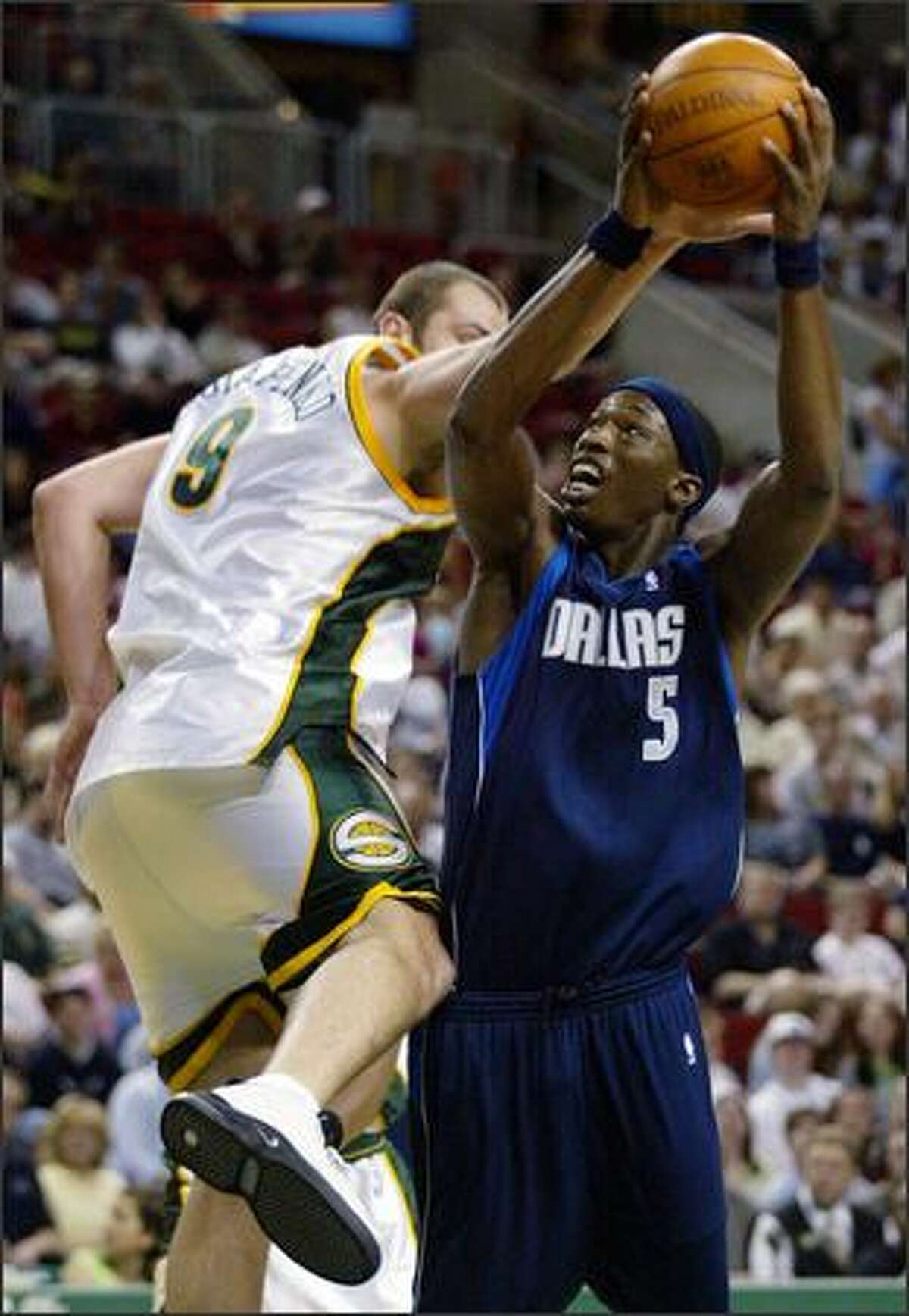 Dallas Mavericks' Josh Howard (5) drives around Seattle SuperSonics' Vitaly Potapenko of Ukraine in the first quarter in Seattle, Saturday, April 10, 2004. (AP Photo/John Froschauer)