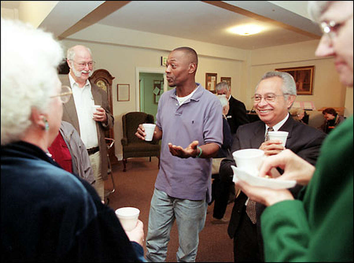 Tent Village resident Ron Fulton, center, mingles with members of Trinity United Methodist Church after services.