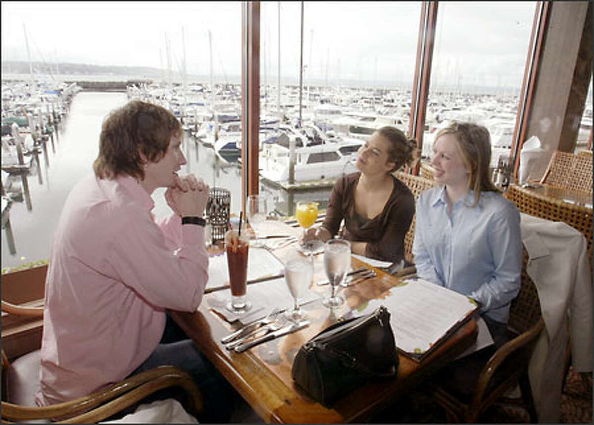 Jason Unck talks with Angie Buckline, center, and Kathryn Kirkland during Sunday brunch at Palisade. The restaurant offers a spectacular view of Elliott Bay looking south toward Seattle.