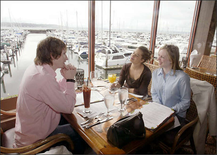 Jason Unck talks with Angie Buckline, center, and Kathryn Kirkland during Sunday brunch at Palisade. The restaurant offers a spectacular view of Elliott Bay looking south toward Seattle. Photo: Jim Bryant, Seattle Post-Intelligencer / Seattle Post-Intelligencer