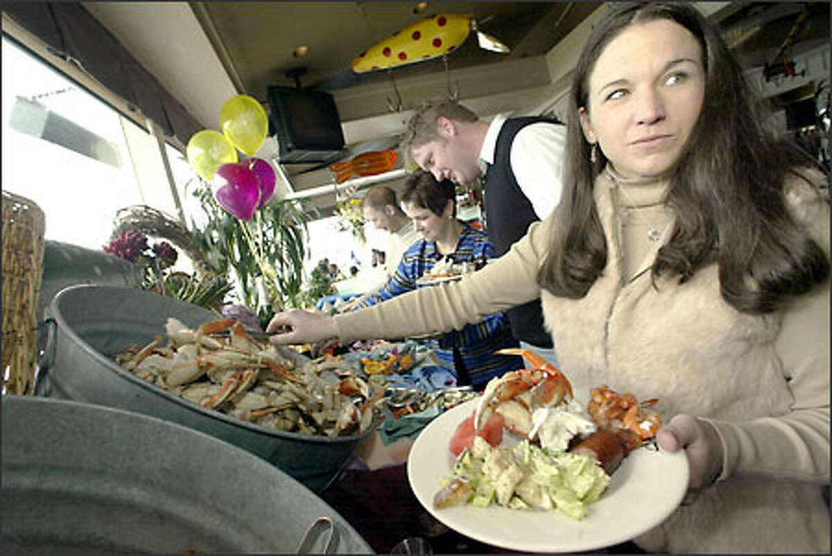 Julie Vanacker loads up on cracked Dungeness crab, one of the highlights of the popular all-you-can-eat buffet brunch served Sundays at Salty's on Alki Beach.