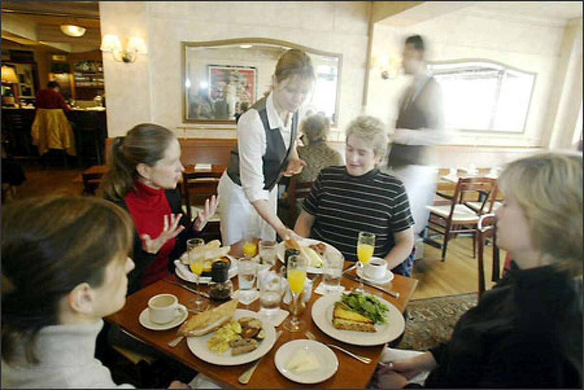 Cafe Campagne attendant Paige Cone serves brunch to Pat Windmill, and,from right,Vicki Baldwin, Kristine Johnson and Elizabeth Kitchens.