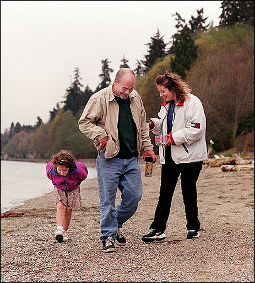 Samantha Smith, 5, Rick Pinson and Dawn Briggs, all of Tacoma, hunt for shells at Owen Bech in Point Defiance Park. Photo: Renee C. Byer, Seattle Post-Intelligencer / Seattle Post-Intelligencer