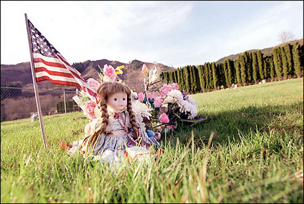 Nicole Embum's grave, 12 miles east of Morton, is decorated with flowers, dolls and a flag. Nicole died after her drug-abusing mother rolled onto her in her sleep