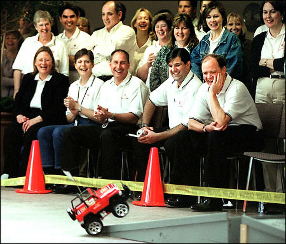 Mike McGavick, Safeco's president and CEO, seated at right, laughs with a group of employees as they watch a remote-controlled model-jeep race.