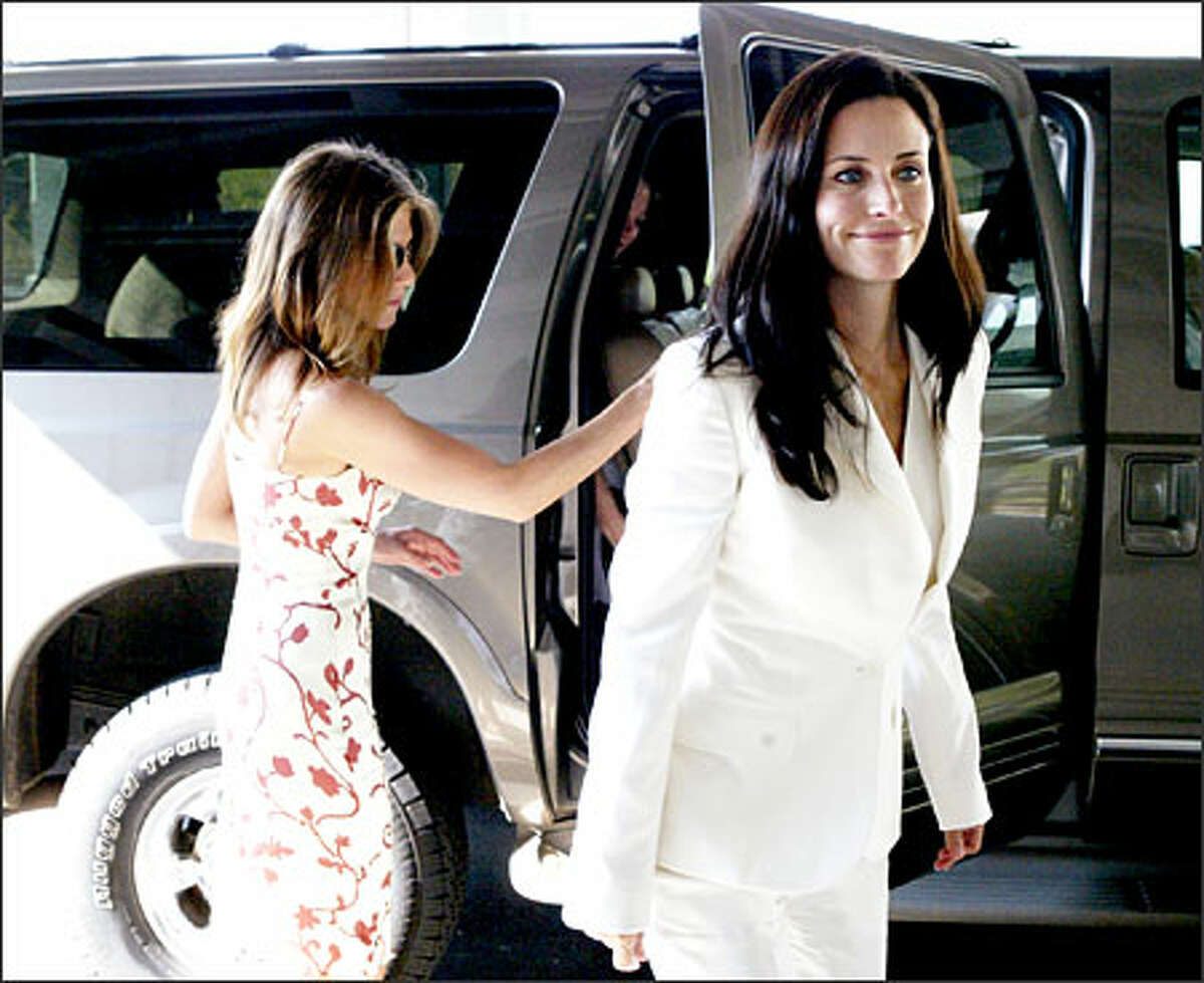 """Jennifer Aniston, left, and Courtney Cox, arrive at a St. Stephen's Episcopal Church in Vestavia Hills, Ala., Saturday for the baptism of Cox's 10-month-old daughter, Coco. Aniston and Cox co-starred on """"Friends"""" and are friends off-screen as well. Cox is a native of Birmingham. (THE BIRMINGHAM NEWS VIA AP)"""