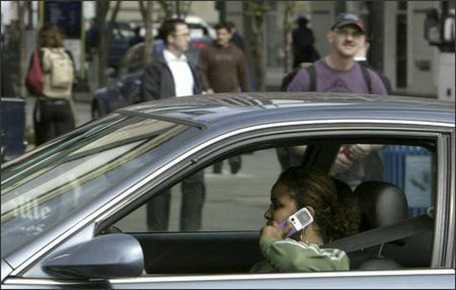 A driver on First Avenue uses a cell phone while driving past the Pike Place Market. State lawmakers hope a new law will at least steer drivers toward hands-free phone devices. Photo: Andy Rogers, Seattle Post-Intelligencer / Seattle Post-Intelligencer