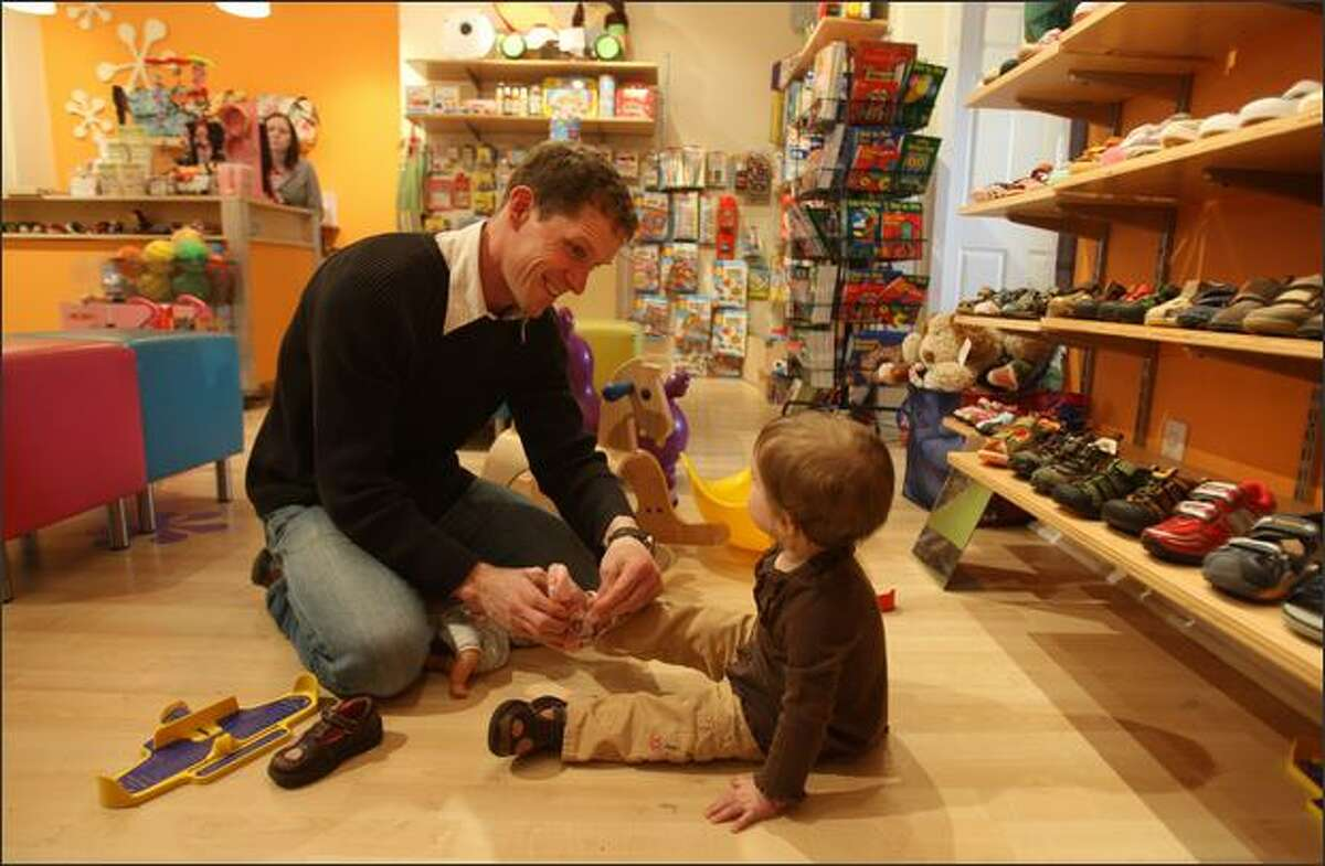 Curtis Kingrey helps daughter Elly, 1, try on a new shoe at Urban Kids Play.