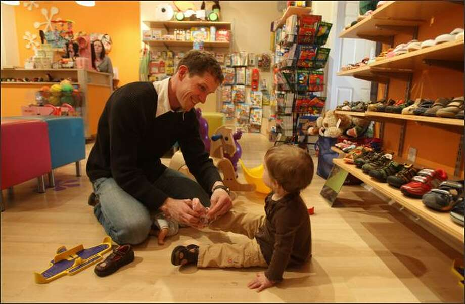 Curtis Kingrey helps daughter Elly, 1, try on a new shoe at Urban Kids Play. Photo: Mike Kane, Seattle Post-Intelligencer / Seattle Post-Intelligencer