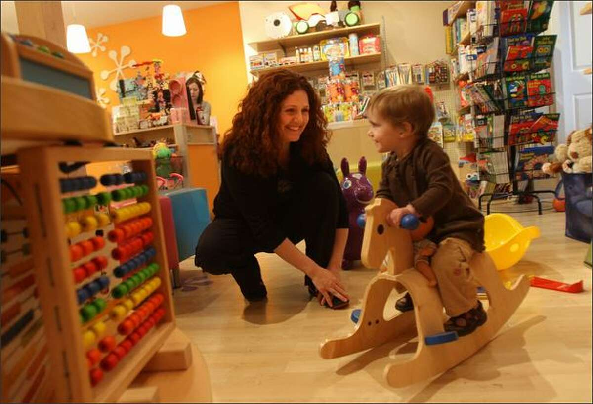 Mikki Kingrey watches daughter Elly, 1, play on a rocking horse in their Queen Anne toy store, Urban Kids Play.