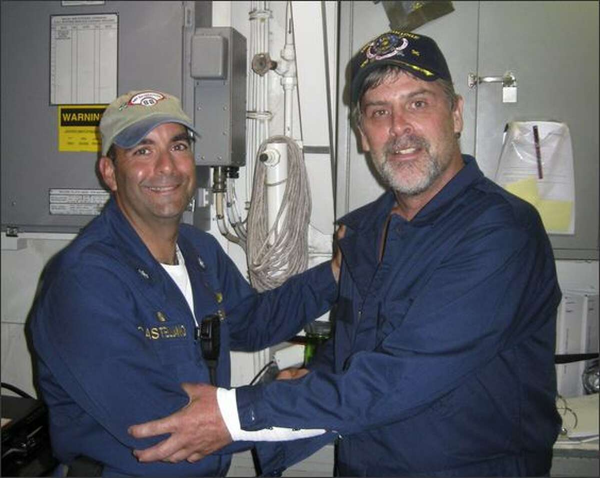 This photo released by the U.S. Navy shows Maersk Alabama Capt. Richard Phillips, right, standing alongside Cmdr. Frank Castellano, commanding officer of the USS Bainbridge, after being rescued by U.S. Naval Forces off the coast of Somalia. Phillips had been held hostage for days by pirates who boarded and briefly took control of his ship several days earlier. (AP Photo/U.S. Navy photo)