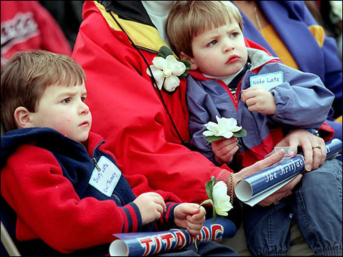 Spectators at the Pacific Science Center, including 4-year-old Scotty Latz, left, and 2-year-old Nicko Latz, watched patiently in yesterday's chilly rain. The boys, local descendents of Titanic passenger Emil Taussig, were among those who selected flowers to toss into the Science Center's ponds.