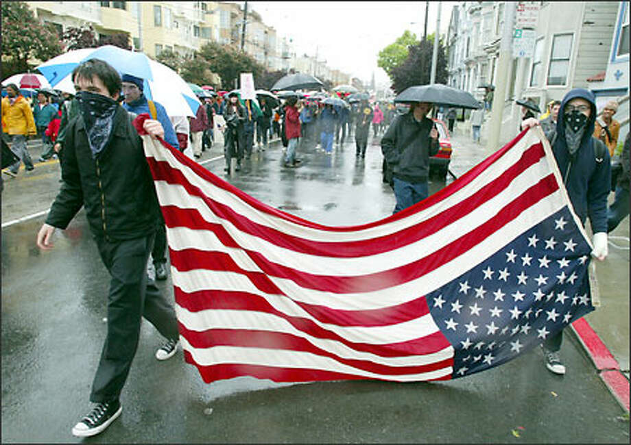 Antiwar protesters drag an upside-down U.S. flag through the rain-soaked streets of San Francisco on Saturday. Photo: Associated Press / Associated Press
