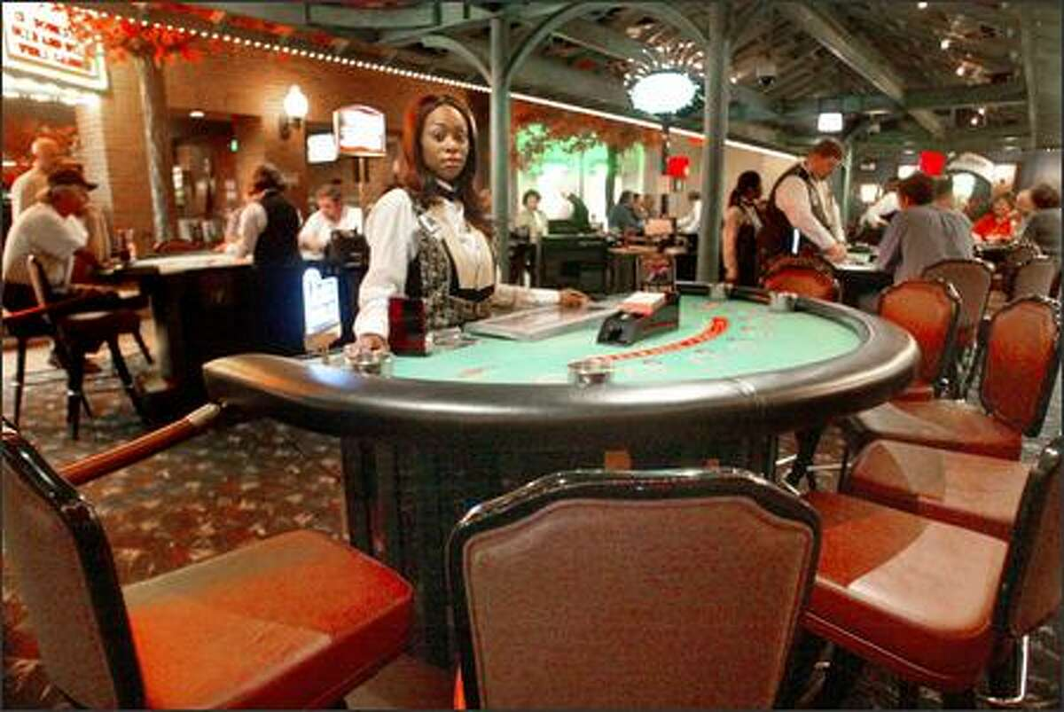Blackjack dealer Eboni Campbell waits for customers at the Grand Central Casino in Lakewood, Pierce County. The casino has laid off 15 employees since the county's smoking ban went into effect, and more layoffs are threatened if a business slump blamed on the ban continues.