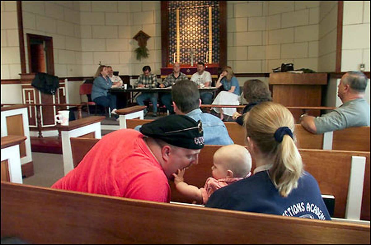 Shane and Kim Maitland, with 7-month-old daughter Madelyn, attend a residents association meeting at which plans for a halfway house for sex offenders were discussed.