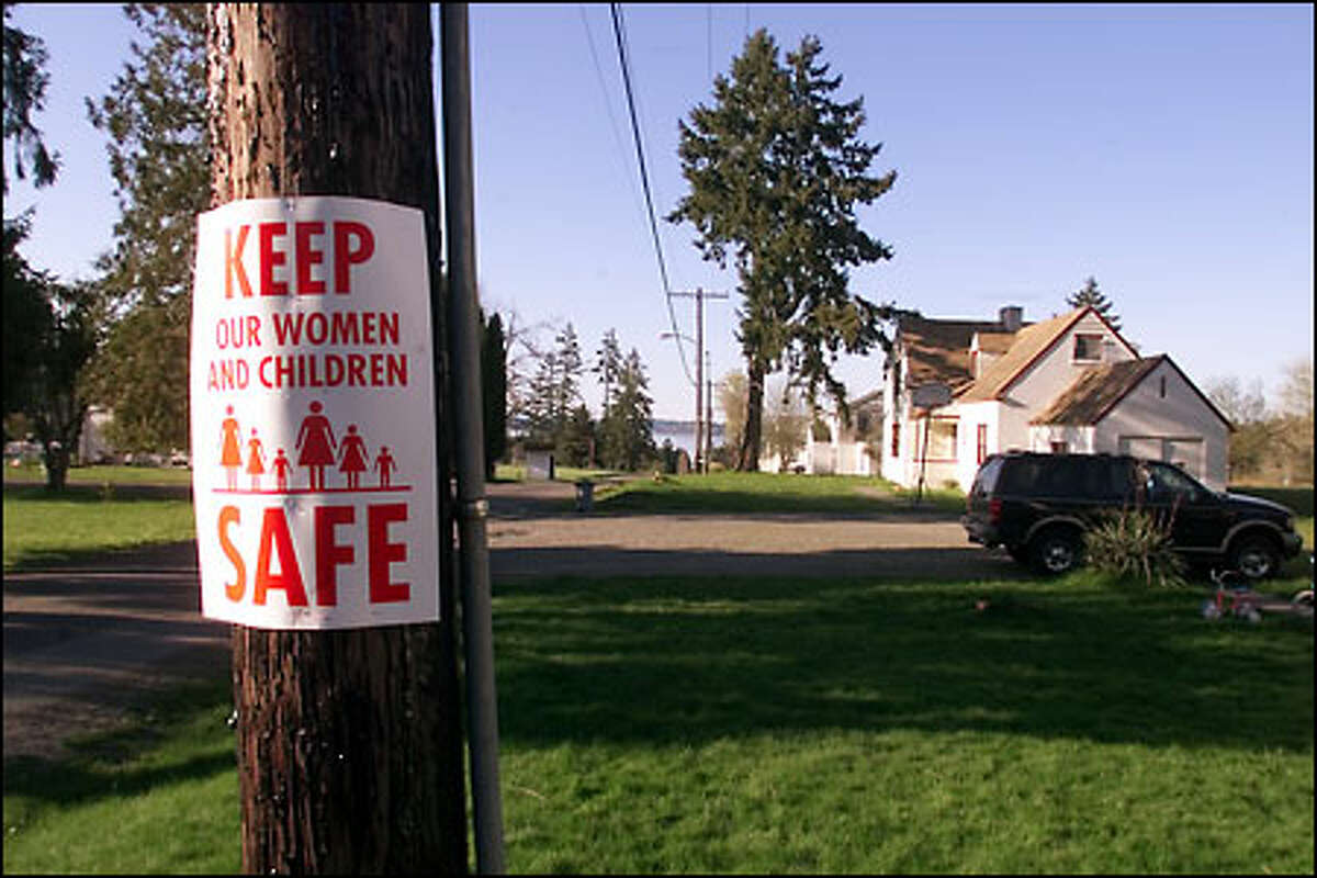 Signs on neighborhood utility poles show opposition to the halfway house for sex offenders on McNeil Island.