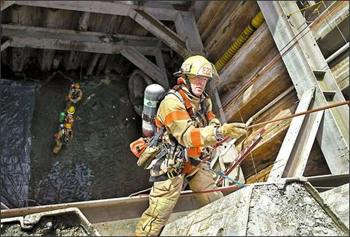 As part of a rescue drill yesterday, the Seattle Fire Department's acting Lt. Russell Wiseman is lowered into a newly built sewer-overflow control tunnel at South Lake Union. The department's tunnel-rescue team was training on the first of four days of an exercise under a federal mandate that requires such teams to actually train in a tunnel.