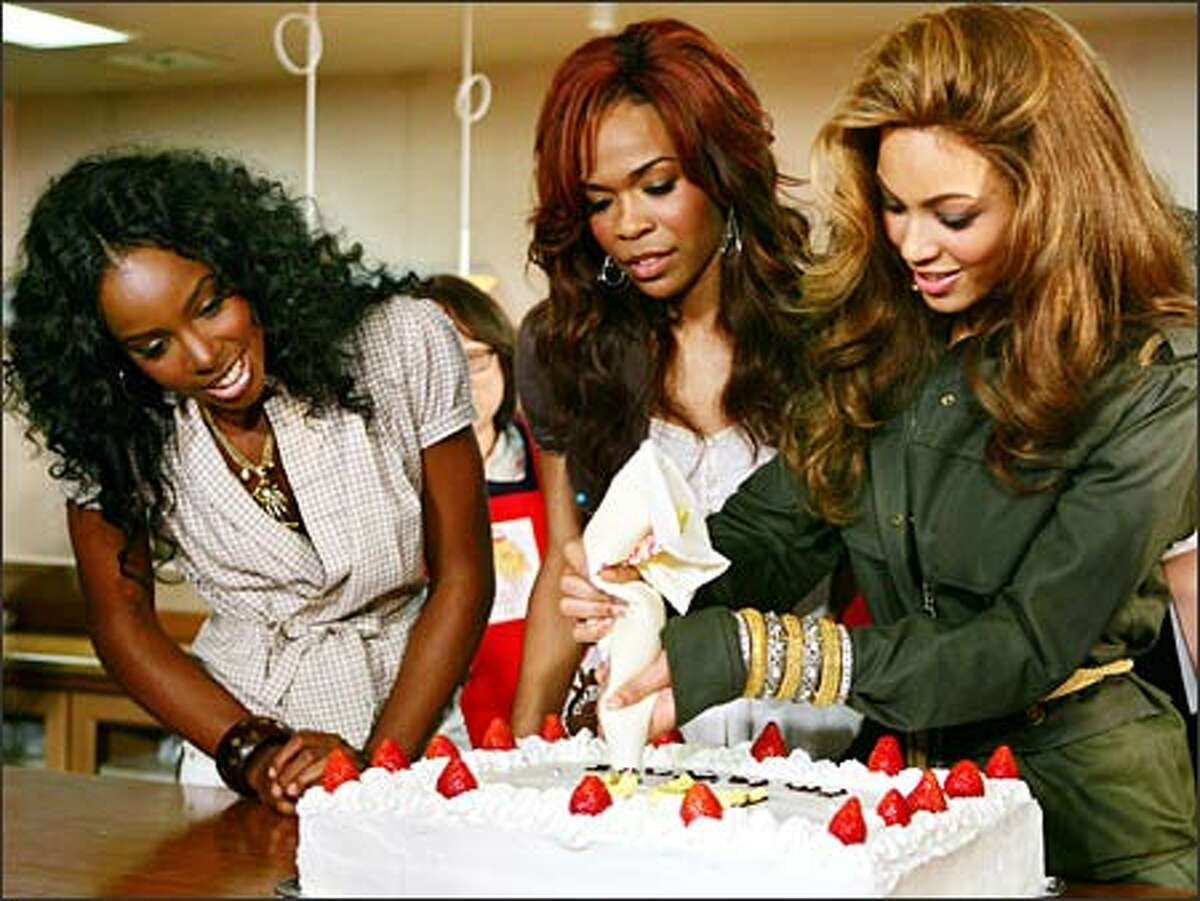 Destiny's Child's members Michelle Williams, left, and Kelly Rowland watch Beyoncé Knowles pipe icing on a cake at the Ronald McDonald House in Tokyo yesterday. The popular R&B group paid a goodwill visit to the house for sick children and their families. (ITSUO INOUYE/AP)