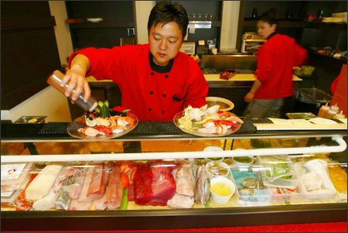 Restaurant owner Jun Hong pours sauce on the Sushi Lover's Combo, which sits next to the Red Fin Combo. The kitchen offers a lengthy, wide-ranging menu.