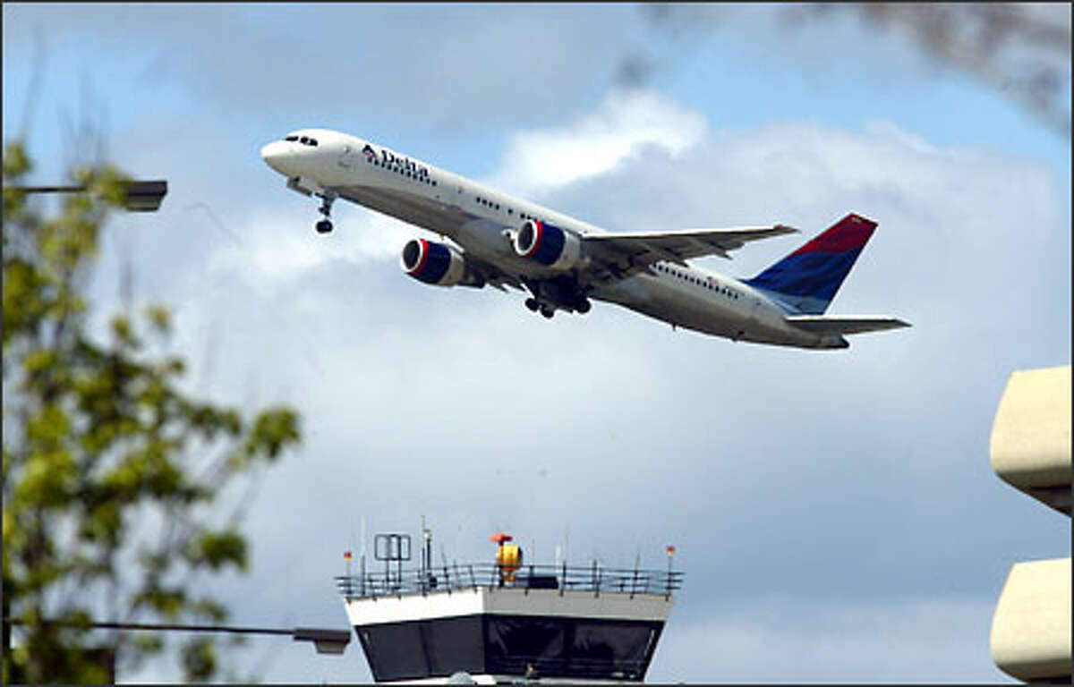 A Delta Air Lines flight leaves Sea-Tac Airport yesterday. The nation's weak economy, war with Iraq and a fear of the SARS illness spreading from Asia have all had an effect on air travel.