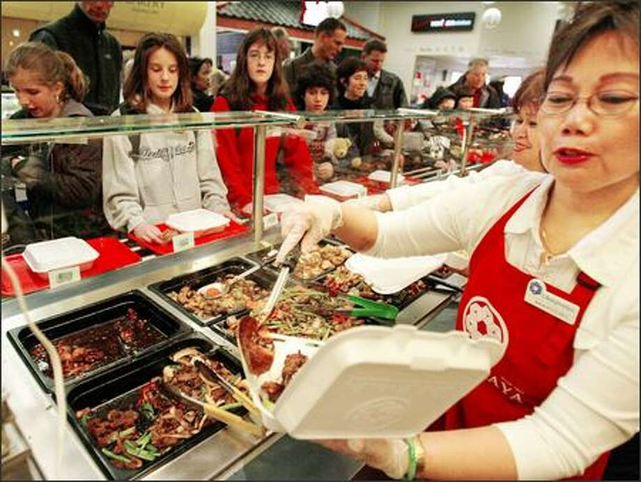 The lunch rush at Uwajimaya's steam table, where people line up for honey-sesame chicken, barbecued meats and sweet-and-sour pork. Tofu and noodle entrees are also good choices. Photo: Paul Joseph Brown, Seattle Post-Intelligencer / Seattle Post-Intelligencer