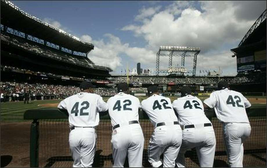 Seattle Mariners players wear No. 42 jerseys in honor of Jackie Robinson as they look out from the dugout before a game against the Texas Rangers in Seattle. From left are: Jason Ellison, Arthur Rhodes, Miguel Batista, Jose Lopez and Adrian Beltre. Robinson broke the color barrier in Major League Baseball 60 years ago Sunday. (AP Photo/Elaine Thompson) Photo: Associated Press / Associated Press