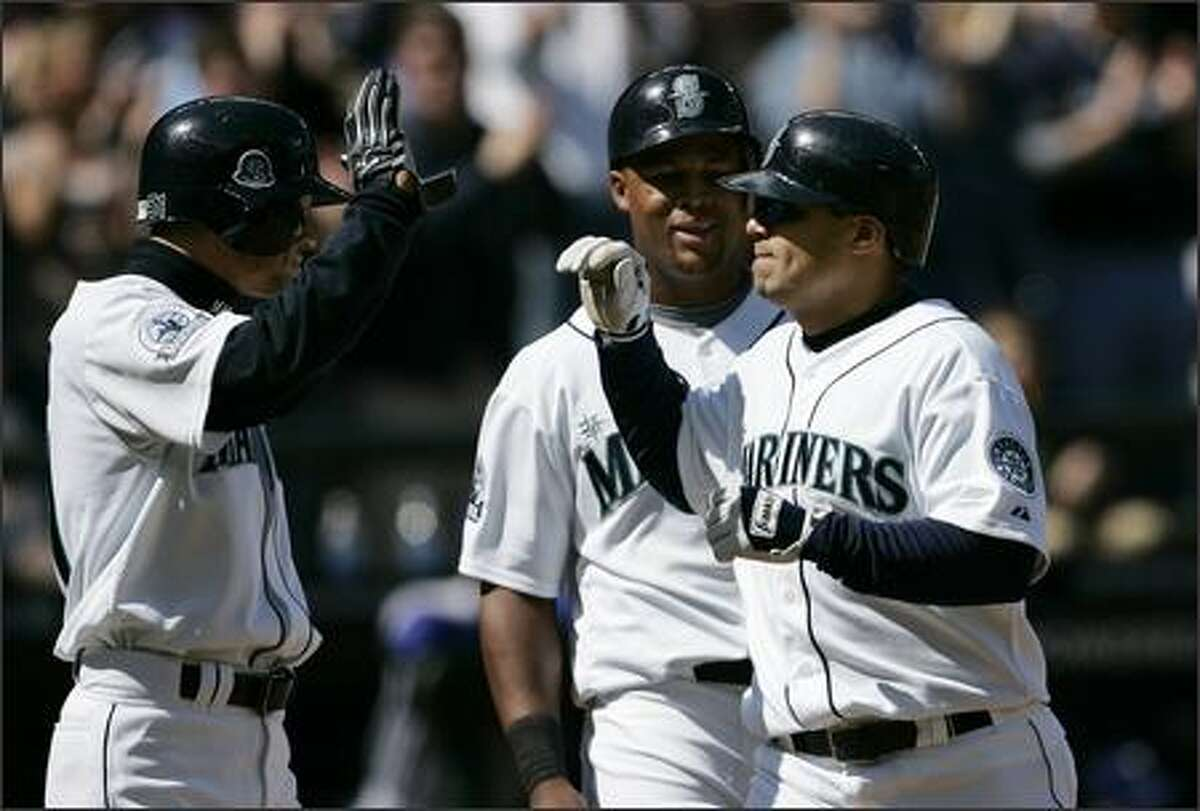 Seattle Mariners' Jose Vidro, right, is greeted at home by the players he batted in on his 3-run home run against the Texas Rangers in the second inning. Ichiro Suzuki, left, and Adrian Beltre each singled earlier in the inning. (AP Photo/Elaine Thompson)